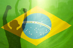 Brazilian Celebrating Arms Raised Behind Flag Stock Photos