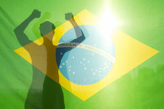 Brazilian Celebrating Arms Raised Behind Flag Stock Photography