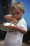 Brazilian child eating from saucepan. LABREA, BRAZIL - April 26, 1997. Brazilian child eating from a saucepan. Amazonia, Brazil Royalty Free Stock Photos