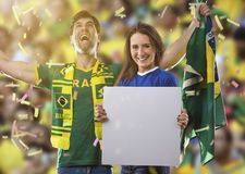 Brazilian couple holding white empty boards on a stadium on a soccer game royalty free stock photo