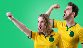 Brazilian couple fan celebrating on green background Stock Image