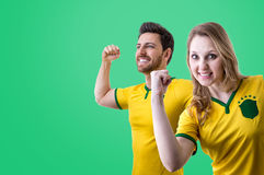 Brazilian couple fan celebrating on green background Royalty Free Stock Images