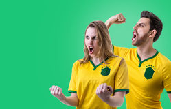 Brazilian couple fan celebrating on green background Stock Photo