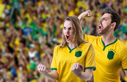 Brazilian couple fan celebrating in the stadium Stock Photo