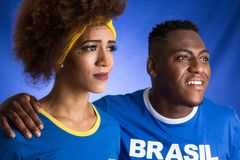 Brazilian couple fans celebrating on soccer match on blue background. Brazil colors. Man wearing generic brandless generic blue royalty free stock image