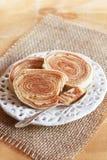 Brazilian dessert Bolo de rolo (swiss roll, roll cake) on white. Brazilian dessert Bolo de rolo (swiss roll, rollcake) on white plate sackcloth. Selective focus royalty free stock photo