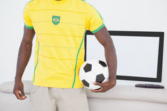 Brazilian fan holding ball in front of tv Stock Photo