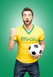 Brazilian fan holding a soccer ball celebrates on green background Stock Photography