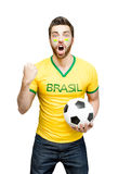 Brazilian fan holding a soccer ball celebrates on white background Stock Image