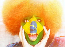 Brazilian fan in the sun. Portrait of a happy brazilian girl with a painted flag Stock Images