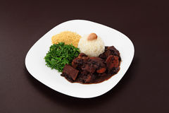 Brazilian Feijoada with garlic. Brazilian Feijoada dish on brown background stock photo