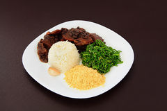 Brazilian Feijoada on a plate. On brown leather background stock photography