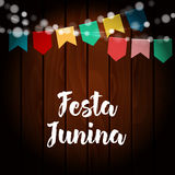 Brazilian Festa Junina greeting card, invitation. Party decoration, string of lights, paper flags. Old wooden background. Brazilian Festa Junina greeting card Stock Photos