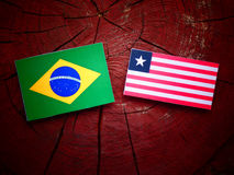 Brazilian flag with Liberian flag on a tree stump isolated. Brazilian flag with Liberian flag on a tree stump Royalty Free Stock Photos