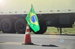 Brazilian flag on a red traffic cone of a highway with a blurred. Truck on background. Image concept to the stoppage and protest of the truck drivers on the Royalty Free Stock Images