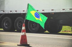 Brazilian flag on a red traffic cone of a highway with a blurred. Truck on background. Image concept to the stoppage and protest of the truck drivers on the Stock Photography
