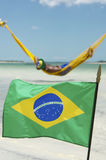 Brazilian Flag Waving in front of Beach Hammocks Stock Images