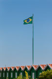 Brazilian Flag in the wind over little green wooden houses. Brazilian Flag in the wind on a flagpole over little green wooden houses blue sky in backgruond royalty free stock photography