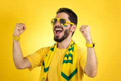 Brazilian supporter of National football team is celebrating, ch. Brazilian football fan emotions: celebrating, excited, happy. Supporter of Brazil national Royalty Free Stock Images