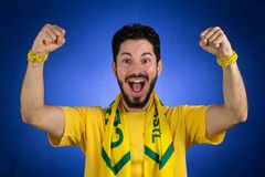 Brazilian supporter of National football team is celebrating, ch. Brazilian football fan emotions: celebrating, excited, happy. Supporter of Brazil national Stock Photography