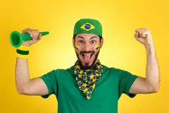 Brazilian supporter of National football team is celebrating, ch. Brazilian football fan emotions: celebrating, excited, happy. Supporter of Brazil national Royalty Free Stock Photos
