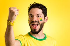 Brazilian supporter of National football team is celebrating, ch. Brazilian football fan emotions: celebrating, excited, happy. Supporter of Brazil national Royalty Free Stock Photography