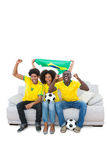 Brazilian football fans in yellow cheering on the sofa Stock Image