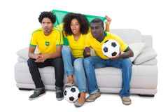 Brazilian football fans in yellow sitting on the sofa Stock Image