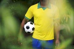 Brazilian Football Player Holding Soccer Ball in Jungle Stock Photos