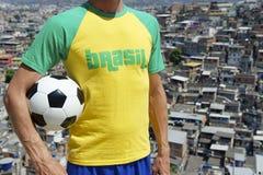 Brazilian Football Player Soccer Ball Favela Slum. Brazilian football player standing in Brasil t-shirt holding soccer ball in front of favela slum background in Stock Photo