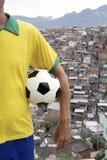 Brazilian Football Player Soccer Ball Favela Slum. Brazilian football player standing in uniform holding soccer ball in front of favela slum background in Rio de Royalty Free Stock Photo