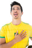 Brazilian football player in yellow singing to anthem Stock Photography