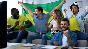 Brazilian friends celebrating goal of football team, watching match at home stock photography
