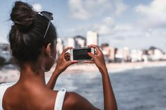 Brazilian girl is photographing coast on her cellphone royalty free stock images