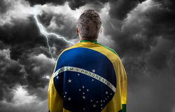 Brazilian holding the flag of Brazil on bad day Royalty Free Stock Photography