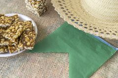 Brazilian june feast sweets called kid foot, a green flag and a straw hat royalty free stock photography