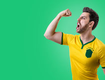 Brazilian male fan celebrating on green background Royalty Free Stock Photo