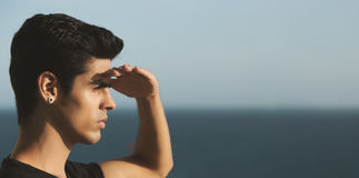 Brazilian male looking into distance. Young handsome brazilian guy with black hair and earring standing in front of ocean and looking into distance shielding his Stock Photo