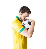 Brazilian man celebrates kissing a soccer ball on white background stock photo