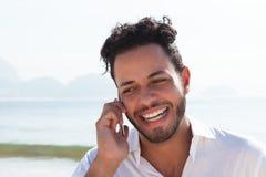 Brazilian man at Copacabana beach talking at phone Stock Photos