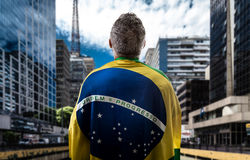 Brazilian man holding the flag of Brazil in Sao Paulo Stock Photos