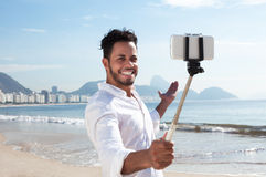 Brazilian man making Selfie with a stick at Copacabana beach. At Rio de Janeiro with ocean in the background Stock Photography