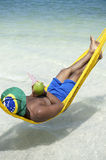 Brazilian Man Relaxing in Beach Hammock with Drinking Coconut Royalty Free Stock Image