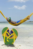 Brazilian Man Relaxing in Beach Hammock Over Sea Stock Photo