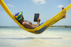 Brazilian Man Relaxing with Tablet in Beach Hammock. Brazilian man using tablet computer relaxing in hammock on beach over the sea Stock Photo