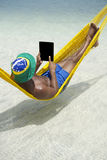 Brazilian Man Relaxing Using Tablet in Hammock on Beach Stock Image