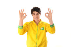 Brazilian man signing ok or zero. Attractive football fan with Brazil flag on his yellow sport blouse. Isolated on white Royalty Free Stock Photos