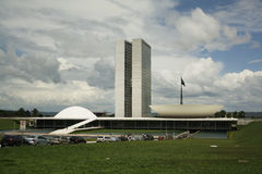 Brazilian National Congress. Over a cloudy sky with the green field in the front Royalty Free Stock Photos