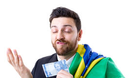 Brazilian not so happy holding Brazilian money and the flag of Brazil Royalty Free Stock Image