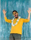 Brazilian party is raising his arms and shouting. Man in green a. Bearded man in green and yellow clothes, sunglasses and Hawaiian necklace. Carnival of Brazil Royalty Free Stock Photos